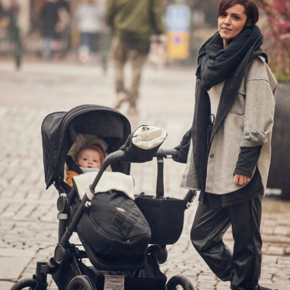 A woman with a pram with a baby inside a Najell Footuff