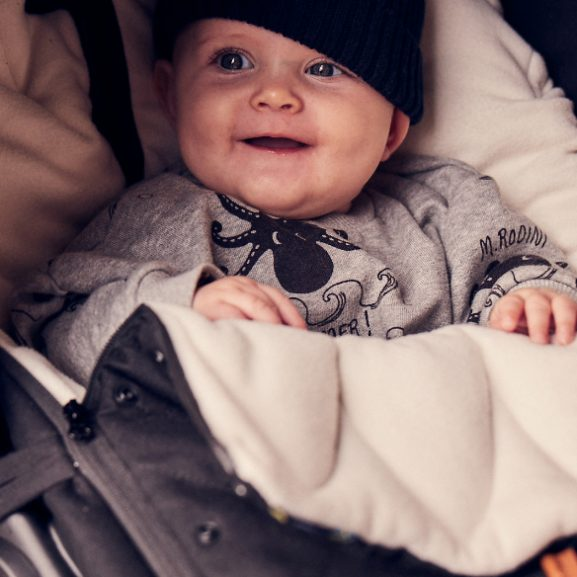A Smiling baby inside a Najell Footmuff