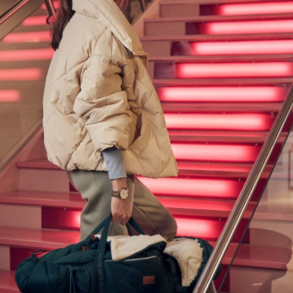 Woman walking in stairs while carrying a Najell SleepCarrier