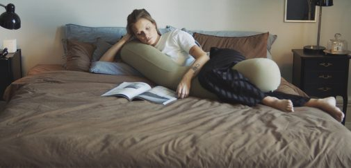 woman using najell pregnancy pillow and listening to podcasts about parenthood